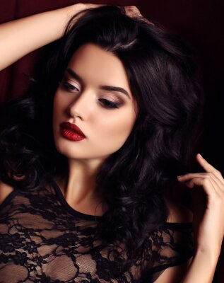 Poster woman with dark hair and evening makeup, wears luxurious black lace dress