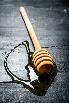 Poster Wooden spoon of sweet natural honey.