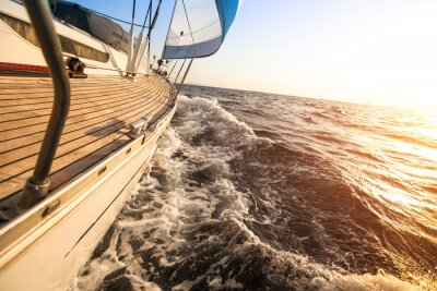 Poster Yacht sailing towards the sunset. Luxury yachts.
