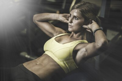 Poster Young fit woman excecising ingym