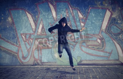 Poster Young man jumping with graffiti in the background
