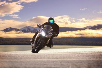 Poster young man riding big bike motorcycle against sharp curve of asph