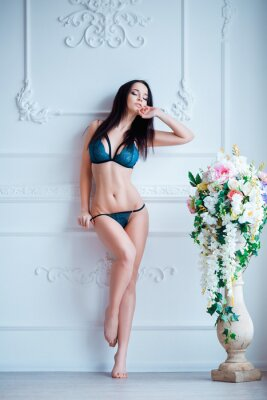 Poster Young, sexy woman with hot body posing in lingerie at luxury interior close to flowers.