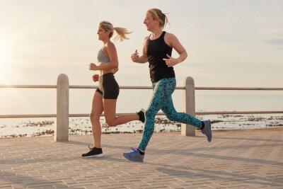Poster Young women running along a seaside promenade