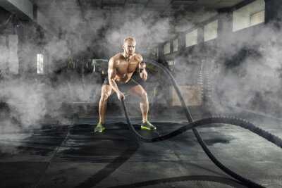 Sticker Athletic young man with battle rope doing exercise in the fitness gym. Sports concept.