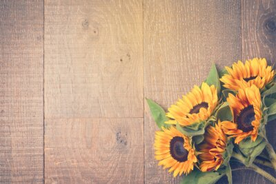 Sticker Autumn background with sunflowers on wooden table. View from above. Retro filter effect