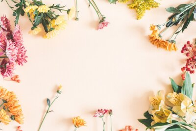 Sticker Autumn composition. Frame made of fresh flowers on pastel beige background. Autumn, fall concept. Flat lay, top view, copy space
