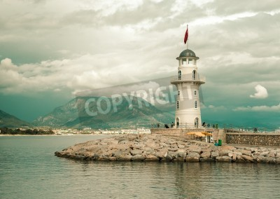 Sticker Beautiful nature landscape with mountains range, cloudy sky and lighthouse in port Alanya, Turkey