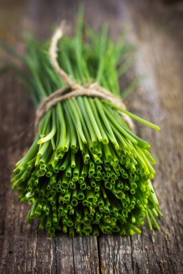 Sticker bunch of  chives on a wooden cutting board