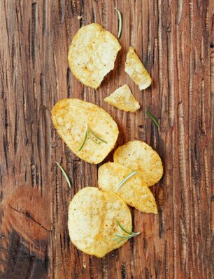 Sticker Chips with salt and rosemary on wooden surface