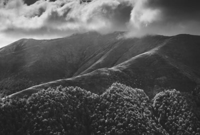 Dark low clouds above the mountains. Black and white