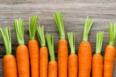Sticker Fresh carrots bunch on rustic wooden background.