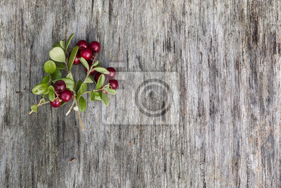 Sticker Fresh ripe cranberries with leaves lying on the old vintage wooden table. Background for nature themes. Horizontal overhead view.