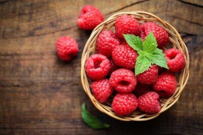 Sticker Fresh ripe red raspberries in a wicjer bowl on dark rustic wooden background