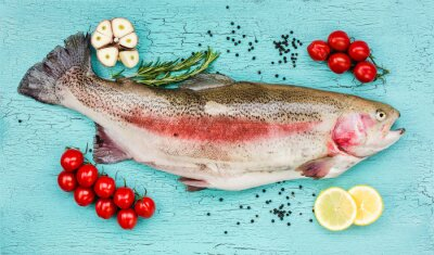 Sticker Fresh trout fish with vegetables on blue wooden table. Top view