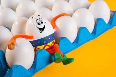 Funny Easter egg boy siting on the tray with eggs