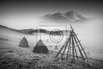 Haystacks in a misty valley. Black and white