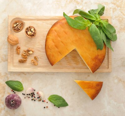 Sticker head of smoked Suluguni cheese on wooden Board with walnuts and