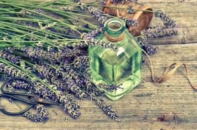 Sticker Herbal lavender oil with fresh flowers on wooden background