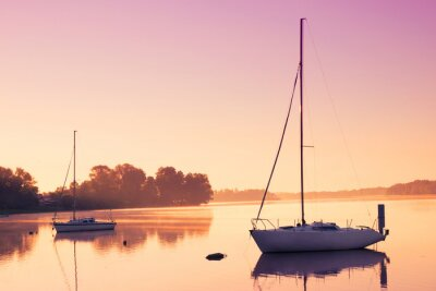 Sticker Little sailing boats reflect in  the serene water during sunrise.