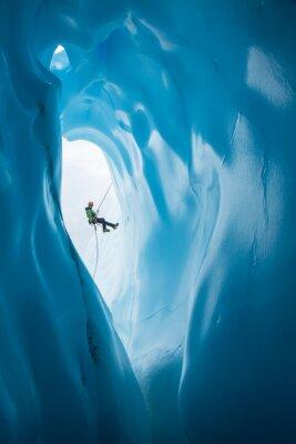 Sticker Man Rappelling past opening of blue ice cave on Matanuska Glacier, Alaska