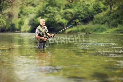 Sticker Mature fisherman fishing in a river with a fishing rod