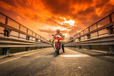 Sticker Moto da strada pronta alla partenza sotto un cielo rosso al tramonto