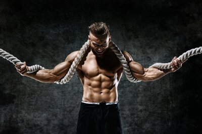 Sticker Muscular man with rope. Photo of man with perfect body after training. Fashion style
