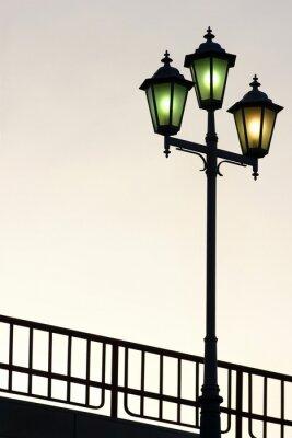 Sticker Old street lamppost against twilight background