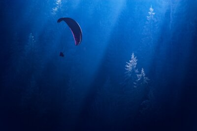 Parachutist silhouette gliding over the foggy forest