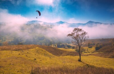 Paraglide silhouette flying above foggy carpathian hills