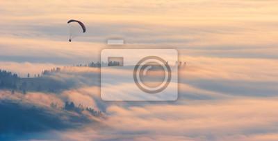 Paraglider over the dense morning fog
