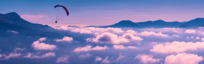 Paraglider silhouette flying above the clouds