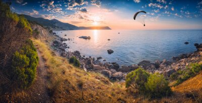 Paraglider silhouette flying over the sea