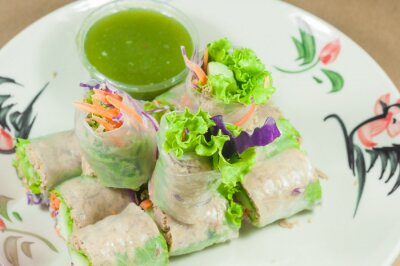 Sticker Portion of spring rolls on old wood with spicy sauce, vegetables
