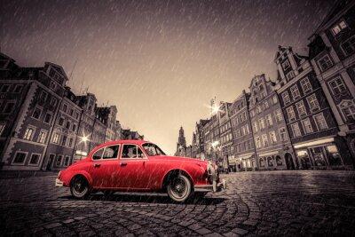 Sticker Retro red car on cobblestone historic old town in rain. Wroclaw, Poland.
