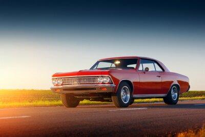 Sticker Retro red car stay on asphalt road at sunset