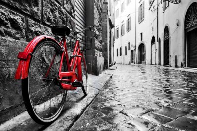Sticker Retro vintage red bike on cobblestone street in the old town. Color in black and white