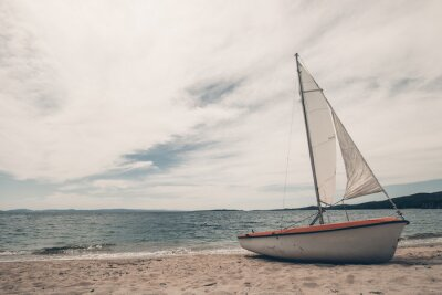Sticker Sail boat on tropical beach with blue water background
