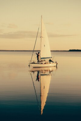 Sticker Sailing boat on a calm lake with reflection in the water. Serene scene landscape.