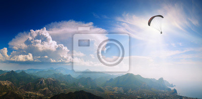 Silhouette of flying paraglider over the Crimea mountain valley
