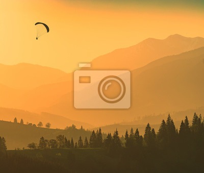 Silhouette of flying paraglider over the mountains