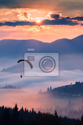 Silhouette of paraglider in the air