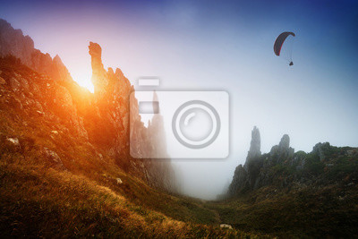 Silhouette of paraglider over the misty mountain valley