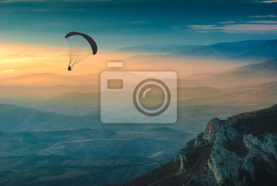 Silhouette of paraglider over the valley