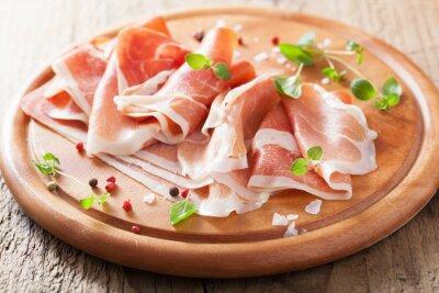Sticker sliced prosciutto ham on chopping board with oregano and pepper