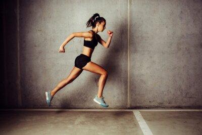 Sticker Slim attractive sportswoman running against a concrete wall