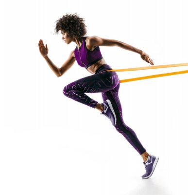 Sticker Strong girl in silhouette using a resistance band. Photo of young african girl performs fitness exercises isolated on white background. Side view