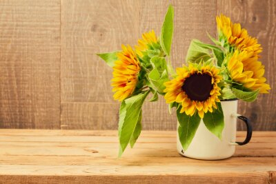 Sticker Sunflowers in vintage cup on wooden table. Autumn background
