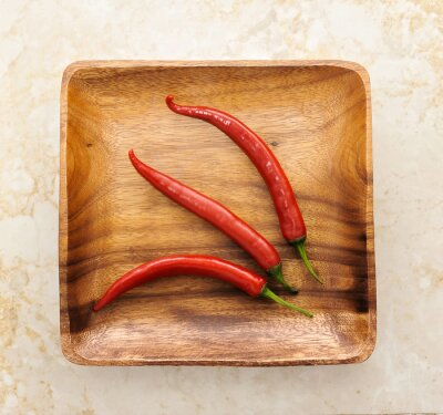 Sticker three cute red hot chili pepper on wood background